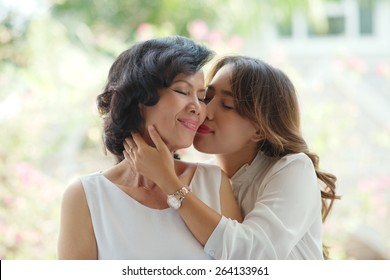 Adult daughter kissing her mature mother