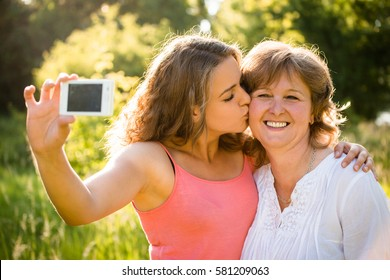 Adult daughter kissing her senior mother while taking selfie photo with mobile phone