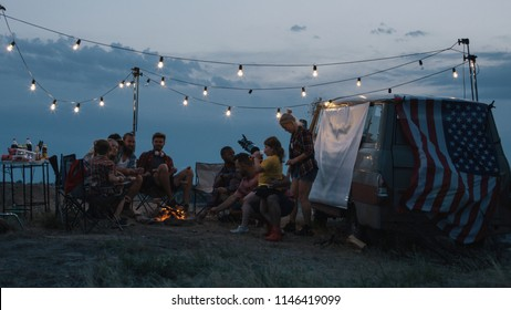 Adult diverse people with childrens gathering around burning bonfire in campsite and frying sausages on skewers in flame sitting under garlands in twilight near van with American flag on trunk.