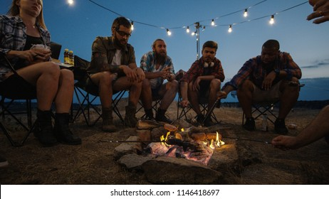Adult diverse people gathering around burning bonfire in campsite and frying sausages on skewers in flame sitting under garlands in twilight