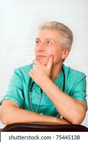 adult doctor in green sitting and wondering