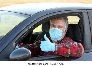 Erwachsene Fahrer mit chirurgischer Schutzmaske und Handschuhe, die mit Daumen vom Auto aus gestillt werden, mit Schutz vor dem Korona-Virus