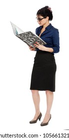 An adult (early 30's) black haired caucasian woman wearing a blue buttoned shirt and and a dark gray skirt, holding a ring binder folder and reading something in it. Isolated on white background.