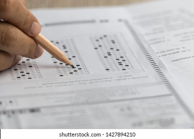 Adult education, educational programs / courses for adults who out of school or college. Older students doing test exam form of standardized multiple choice with answers sheet in life long learning.