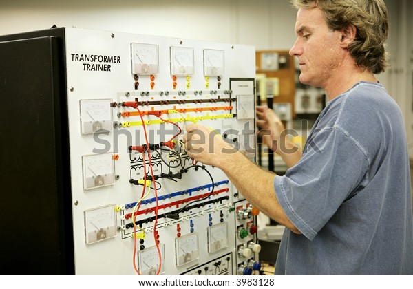 An adult education student learning electronics on a Transformer Trainer Board.