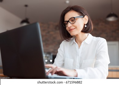 Adult elegant businesswoman in white shirt and glasses sitting with laptop in cafe.