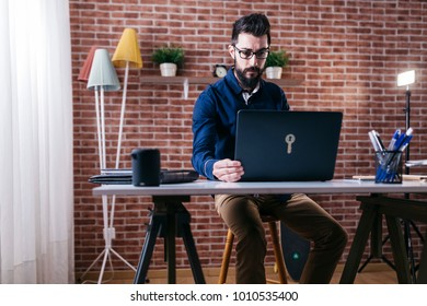Adult elegant man in eyeglasses sitting at table in modern office and using laptop with concentration.