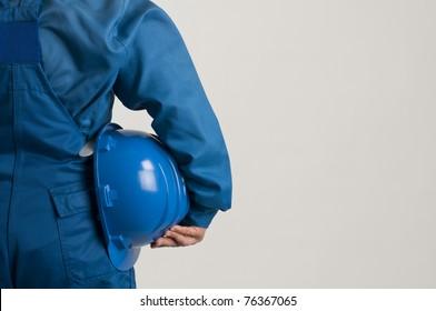 adult engineer holding a blue helmet