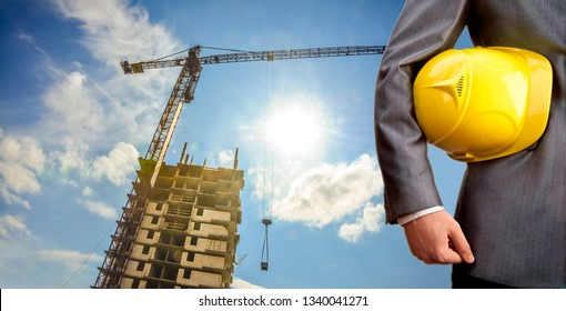 adult engineer or inspector hand holding yellow plastic helmet for workers security over highrise buildings construction cranes on background evening sunset sky Crane lifts load background.No face.