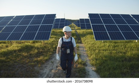 Adult engineer in uniform walking across solar battery panels on green sunny field. Futuristic technology innovation. Ecology and environment concept. Sunlight power. Eco-friendly system.