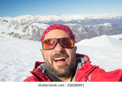 Adult european man taking selfie on snowy slope with the beautiful snowcapped italian Alps in the background. Natural colors.