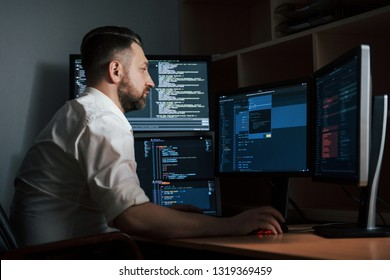 Adult experienced programmer. Bearded man in white shirt works in the office with multiple computer screens in index charts.