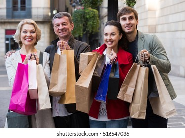 Adult family of four with shopping bags on city street