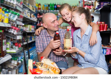 Adult family the supermarket with basket choosing sunflower oil