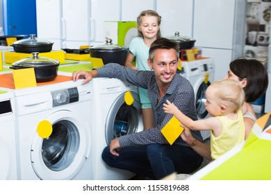 Adult family together choosing washing machine in shop of household appliances