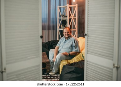 Adult fat white man in denim suit sitting on sofa in room. Man over 40, resting at home.