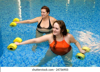 Adult fat  women and young fat woman on group aqua aerobics training in water with dumbbells