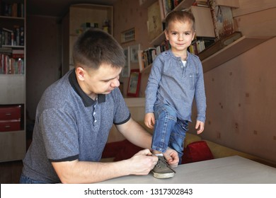 Adult father in grey t-shirt learning his little son in jeans to lace his shoes at home, education and family care, lifestyle portrait