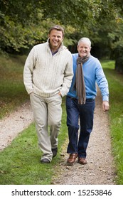 Adult father and on walking along woodland path in autumn