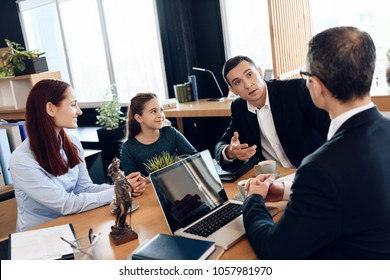 Adult father, red head mother and little smiling daughter are sitting in lawyer's office. Family in office of family lawyer.