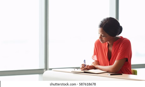 Adult female African writer busy writing in her notebook while wearing a bright orange blouse while seated next to large panes of glass in the business lounge she is seated in.