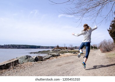 Adult female back facing camera jumps, clicking her heels in enjoyment, along the shoreline in the Atlantic Ocean at Goat Island