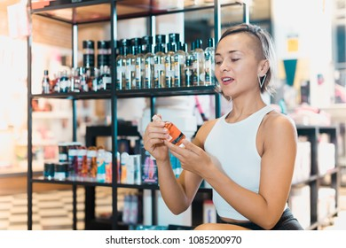 Adult female buyer choosing bottle of pheromones in the sex shop