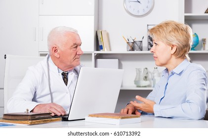 Adult female client having consultation with man doctor in hospital