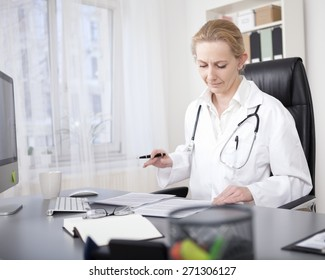 Adult Female Clinician Sitting at her Desk and Reading Back her Written Medical Reports Seriously.