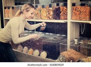 Adult female customer selecting various nuts in the store with ecological goods