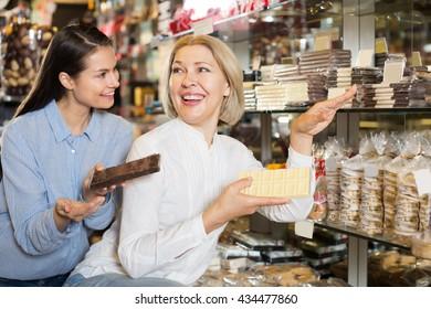 Adult female customers choosing delicious milk chocolate in shelf