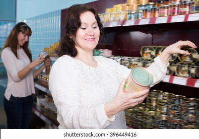 Adult female customers selecting tinned products at grocery