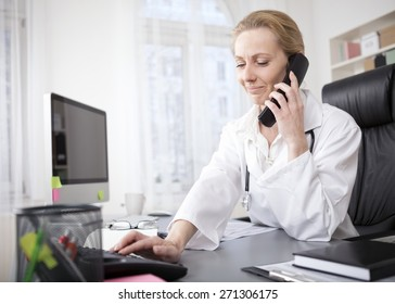 Adult Female Doctor Sitting at her Office While Dialing a Telephone Number of her Patient.