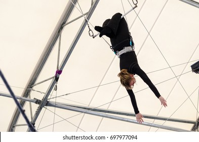 An adult female hangs from her knees on a flying trapeze. The woman is an amateur trapeze artist.
