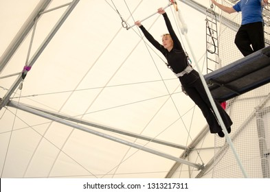 An adult female hangs on a flying trapeze at an indoor gym. The woman is an amateur trapeze artist.