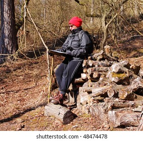 Adult Female Hiker sitting on a pile of timber reading a map