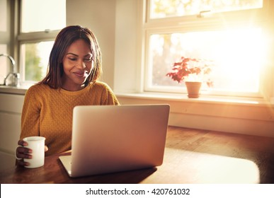 Adult female holding cup and laughing while looking at her laptop computer while sitting near bright sunny window in kitchen