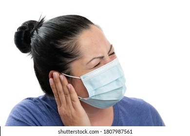 Adult female model touching ear with hand as pain covid19 influenza flu symptom concept wearing surgical disposable mask to protect from contamination isolated on white studio background