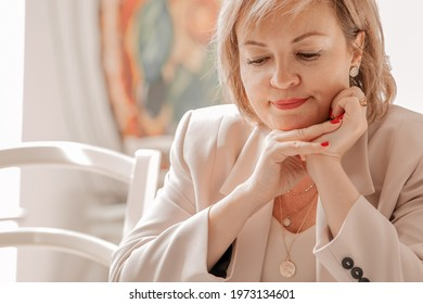 An adult female psychologist-coach sits thoughtfully at a table in the bright interior of a cafe. close-up. the concept of remote work and psychological assistance
