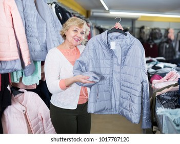 Adult female purchaser choosing windbreaker jackets in the shopping center