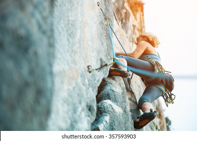 Adult female rock climber on vertical flat wall with poor relief - side view, close-up.