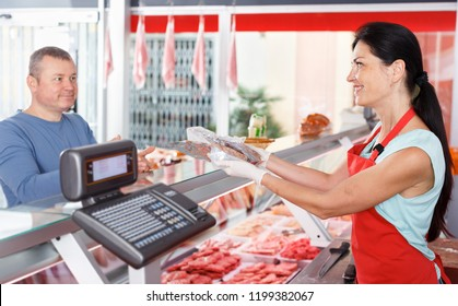 Adult female seller helping male customer choosing different sausages in butcher's shop