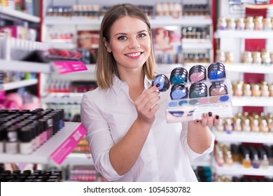 Adult female seller showing eyeshadows in cosmetics shop