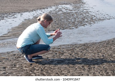 Adult female tourist taking photos on the shore on the beach on the Pacific Ocean at Twin Harbors State Park in West Port, WA, USA.