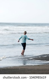 Adult female tourist walking along the shore on the beach on the Pacific Ocean at Twin Harbors State Park in West Port, WA, USA.