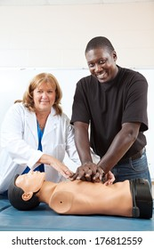 Adult first aid or EMT student practicing CPR on a dummy, with the help of a doctor or nurse.  Vertical with room for text.