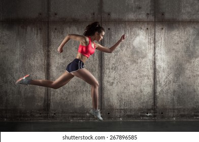 adult fit girl running on dark background