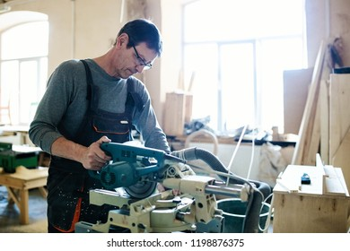 Adult focused man in overall using modern miter saw working on piece of wood in carpentry workshop