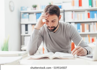 Adult focused man sitting at desk and studying at the library, learning and self improvement concept