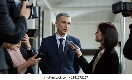Adult formal man of government deputy talking to group of journalists and giving interview with smile looking excited with success